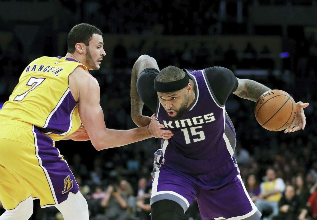 In this Feb. 14, 2017 photo, Sacramento Kings' DeMarcus Cousins, right, drives past Los Angeles Lakers' Larry Nance Jr. during the second half of an NBA basketball game in Los Angeles. A person familiar with the situation said Sunday that the Sacramento Kings have agreed to trade Cousins and Omri Casspi to the New Orleans Pelicans in exchange for Tyreke Evans, 2016 first-round draft pick Buddy Hield, Langston Galloway and first- and second-round draft picks this summer.