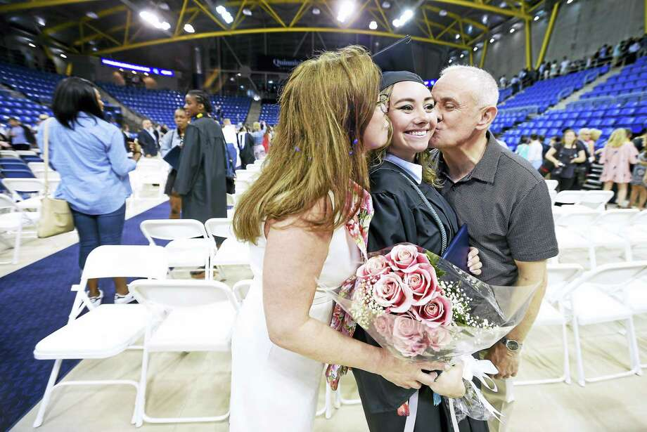 Annemarie Pistilli (left) of Staten Island and her husband, Jonathan (right), kiss their daughter, Rebecca, after commencement exercises for Quinnipiac University's College of Arts and Sciences at the TD Bank Sports Center in Hamden on 5/20/2017. Photo: Arnold Gold — New Haven Register