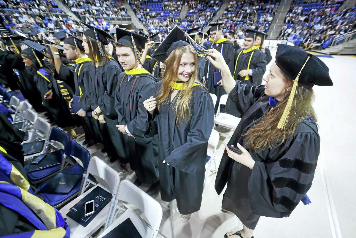 Natalia Krolik (center) gets an assist with her tassel from associate professor of biology Courtney McGinnis at the conclusion of commencement exercises for Quinnipiac University's College of Arts and Sciences at the TD Bank Sports Center in Hamden on 5/20/2017.
