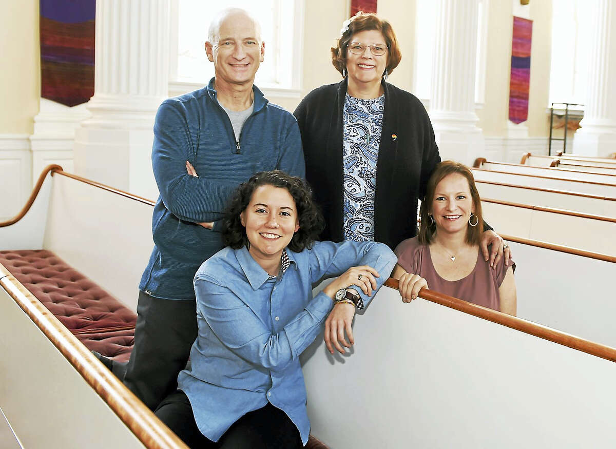Standing, left to right: Tony Forman of the Church of the Redeemer and Kathryn Thomas of the United Church on the Green. Sitting, left to right: Caryne Eskridge of United and Beth Pellegrino of Redeemer. They were photographed in the sanctuary at the Church of the Redeemer in New Haven.