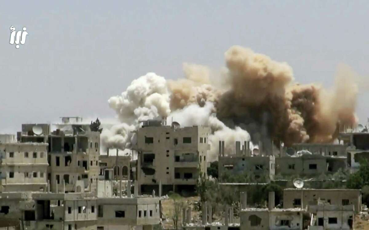 This file frame grab from video provided on Monday, June 12, 2017, by Nabaa Media, a Syrian opposition media outlet that is consistent with independent AP reporting, shows smoke rising over buildings that were hit by Syrian government forces bombardment, in Daraa city, southern Syria. The Syrian military has announced the cessation of all combat operations in the southern city of Daraa for 48 hours in support of national reconciliation.
