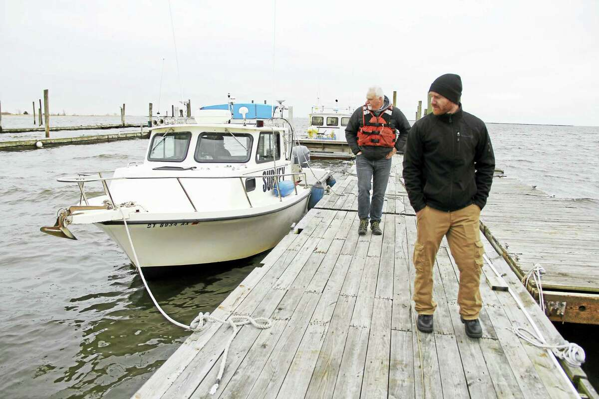 Nick DeLong, left, a nautical archaeologist, and John Bean, a certified hydrographer, walk on dock in Bridgeport Harbor after a morning of surveying three shipwrecks in the harbor.