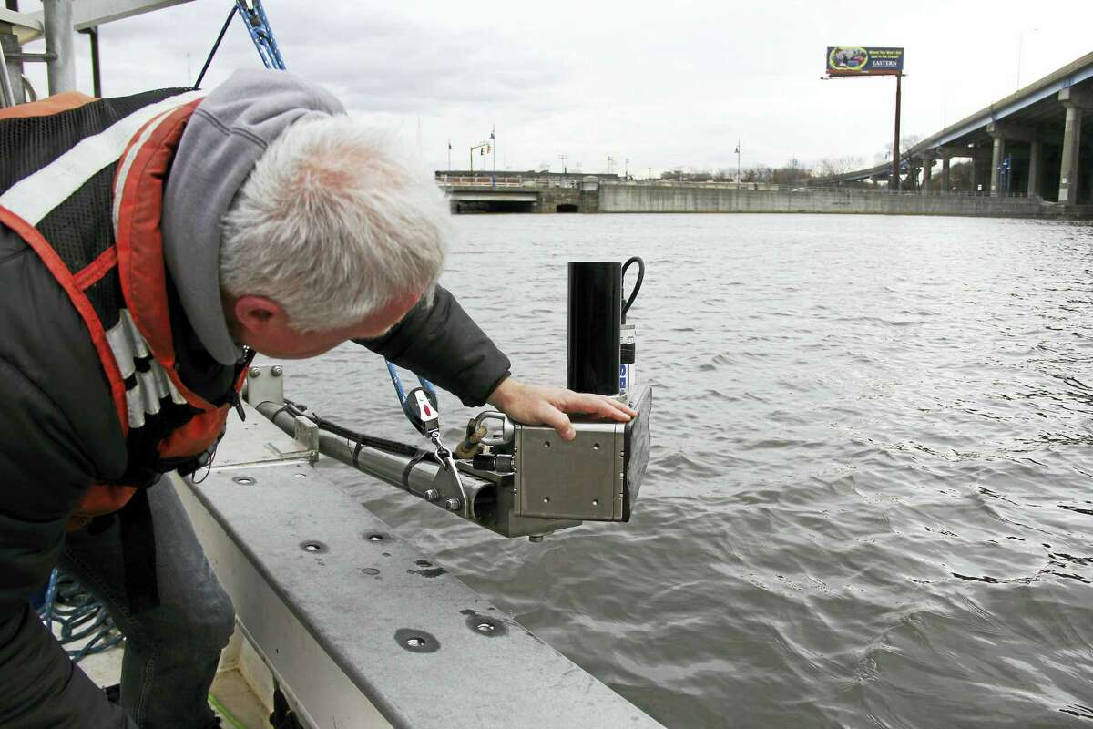 John Bean, a certified hydrographer, inspects a multibeam echosounder in Bridgeport Harbor that is used to create images from echoes created by objects on the ocean floor.