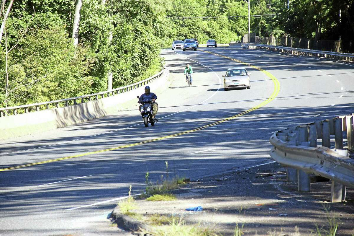 Cars, trucks, bicycles and motorcycles share the road on Newfield Street in Middletown.