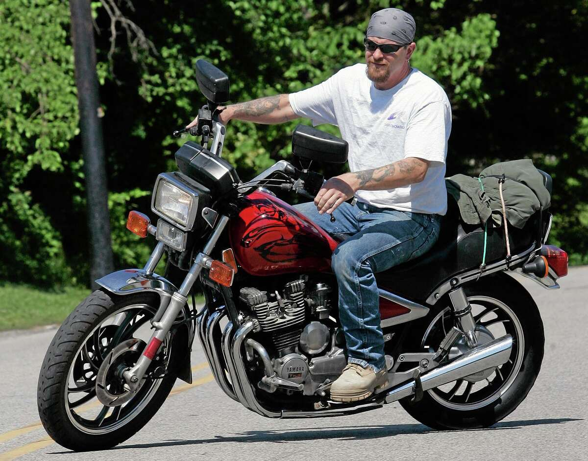 In this file photo, Randy Knauff takes off from work without a helmet on his motorcycle in Harmony, Pa. Across the nation, motorcyclists opposed to mandatory helmet use have been chipping away at state helmet laws for years while crash deaths have been on the rise.