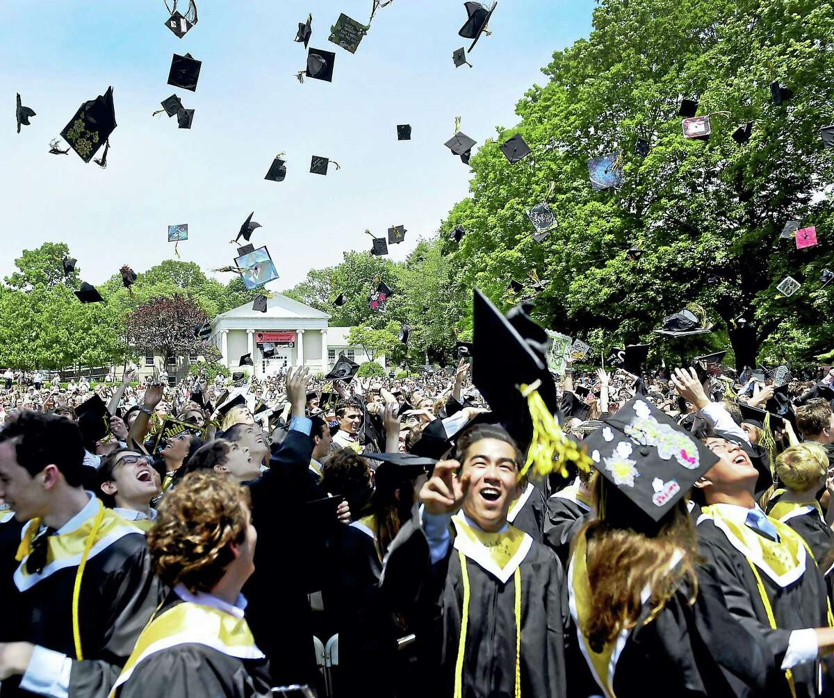 Salutatorian Eric Xia, front left, and valedictorian Anthony Xu, front right, throw their mortarboards in the air as they celebrate near the end of Daniel Hand High School commencement exercises Monday in Madison.
