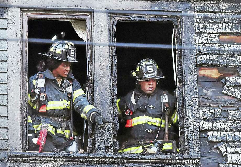 New Haven Firefighter Erika Bogan and Lt. Angel Aviles, members of Engine 5 of the New Haven Fire Department, search for hot spots from the top story of a house at 6 Rowe St. in New Haven Wednesday. Photo: Catherine Avalone — New Haven Register   / Catherine Avalone/New Haven Register