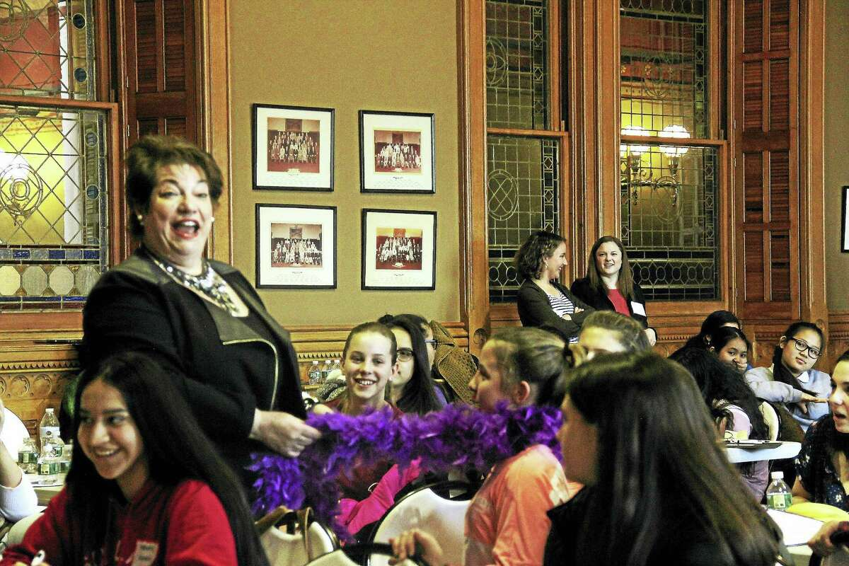 The final speaker of Girls Day at the Capitol Wednesday, Patricia Russo, executive director of the Women's Campaign School at Yale University, wraps a purple boa around the neck of a high school student.