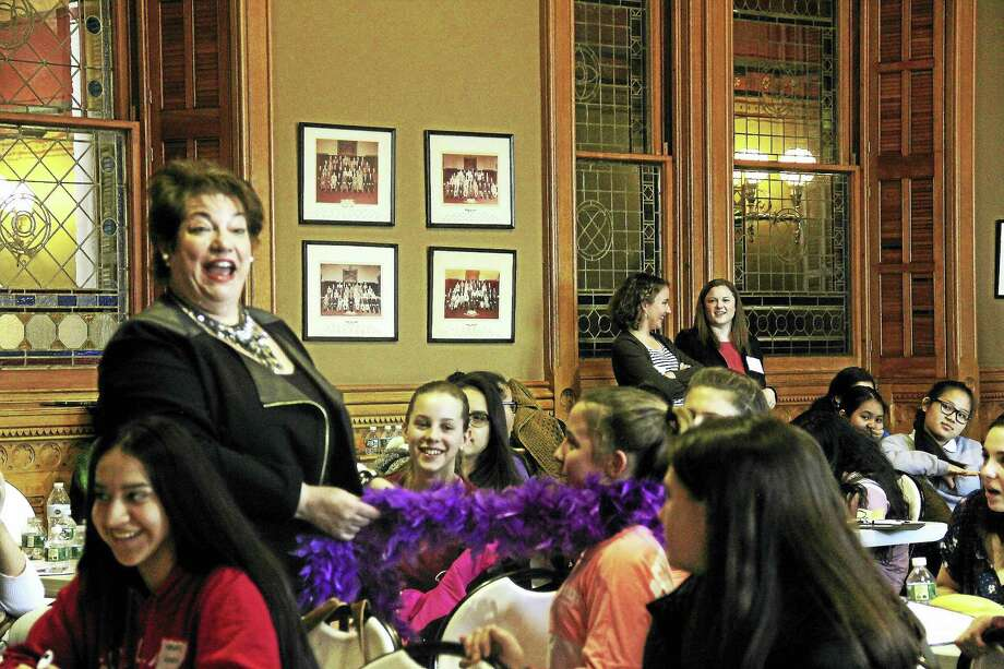 The final speaker of Girls Day at the Capitol Wednesday, Patricia Russo, executive director of the Women's Campaign School at Yale University, wraps a purple boa around the neck of a high school student. Photo: Kathleen Schassler — New Haven Register   / Kathleen Schassler All Rights