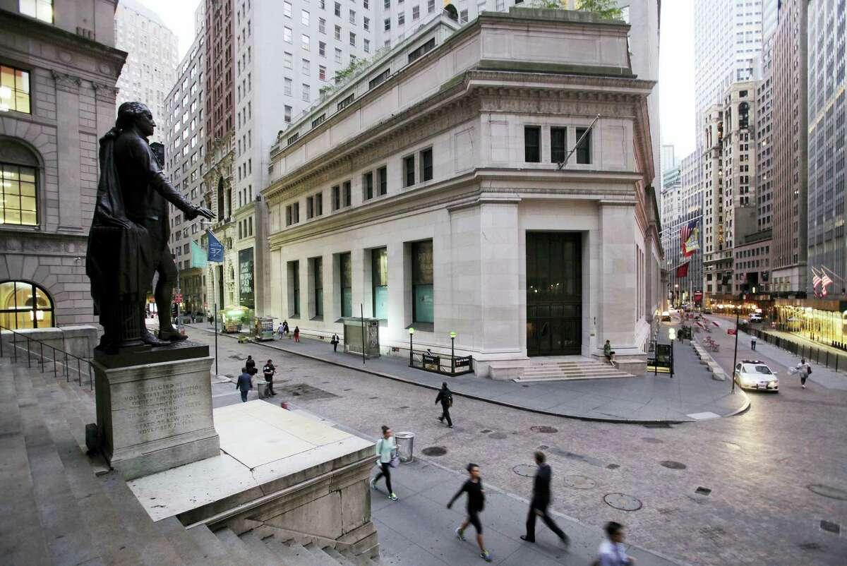 People walk to work on Wall Street beneath a statue of George Washington in New York.