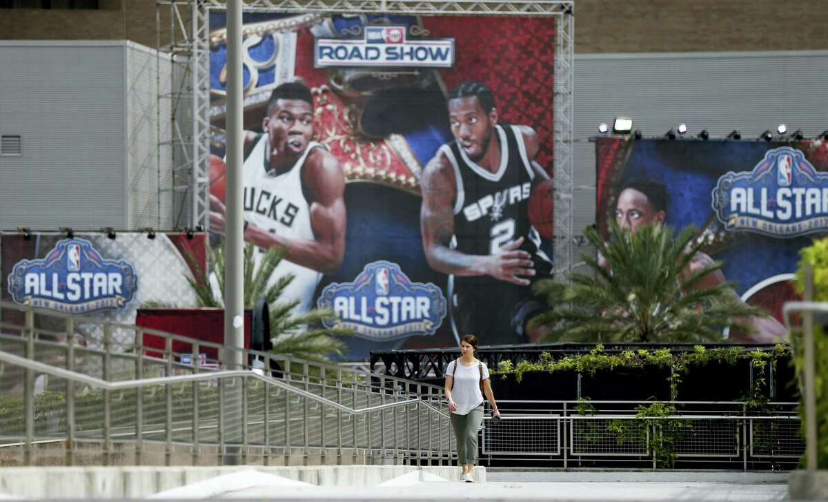 Rachel Seibel walks past signage being put up in preparation for the NBA All Star Game festivities this weekend, in New Orleans on Feb. 14, 2017. Charlotte won't be a ghost town this weekend, but it sure won't be buzzing like many had hoped when the NBA awarded the city the 2017 All-Star game. The league moved the event last summer after North Carolina politicians failed to repeal House Bill 2, a law that passed last March that limits the protections of LGBT people.
