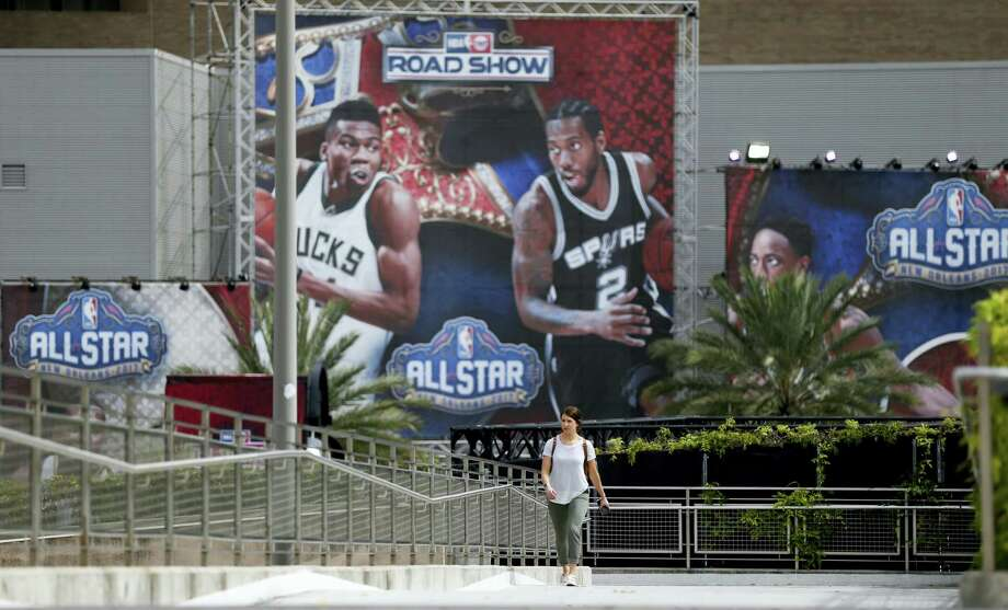 Rachel Seibel walks past signage being put up in preparation for the NBA All Star Game festivities this weekend, in New Orleans on Feb. 14, 2017. Charlotte won't be a ghost town this weekend, but it sure won't be buzzing like many had hoped when the NBA awarded the city the 2017 All-Star game. The league moved the event last summer after North Carolina politicians failed to repeal House Bill 2, a law that passed last March that limits the protections of LGBT people. Photo: AP Photo/Gerald Herbert   / Copyright 2017 The Associated Press. All rights reserved.