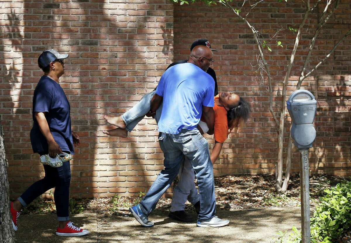 Family members carry a grief stricken Ebony Archie, mother of Kingston Frazier, after learning the young boy was found dead after being kidnapped during the theft of his mother's vehicle from a Kroger parking lot, Thursday, May 18, 2017, in Jackson, Miss.