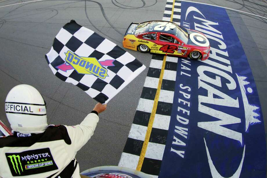 Kyle Larson takes the checkered flag to win the FireKeepers Casino 400 at Michigan International Speedway on Sunday. Photo: Chris Trotman — NASCAR Via AP   / 2017 Getty Images