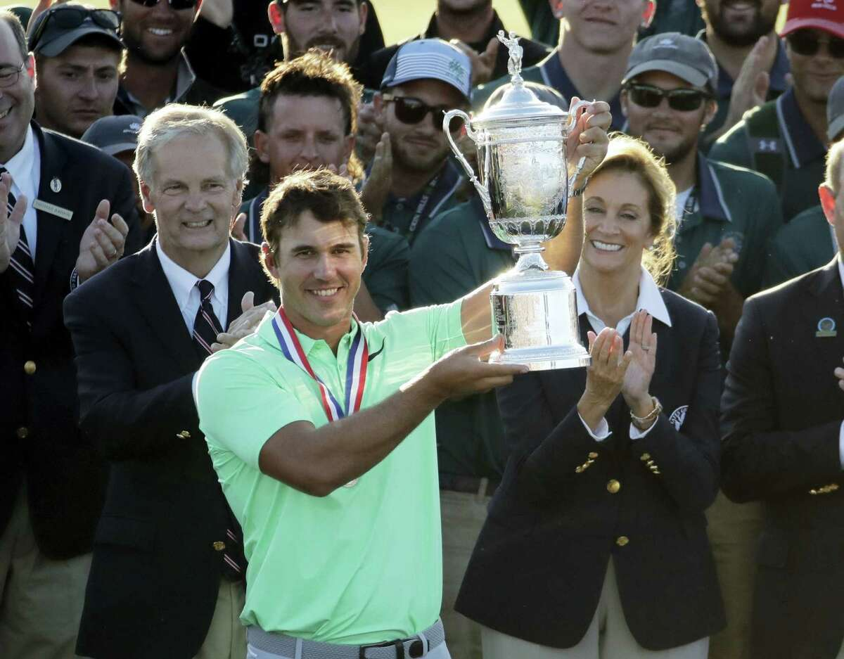 Brooks Koepka holds up the trophy after winning the U.S. Open Sunday at Erin Hills in Erin, Wis.