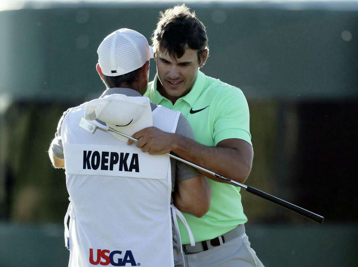 Brooks Koepka is congratulated by caddie Ricky Elliot.