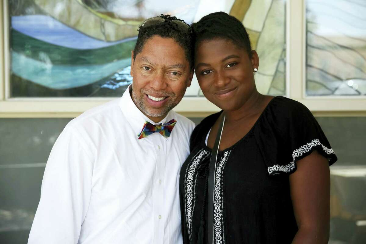 This April 22, 2017 photo provided by Dylan Perot shows Dr. Christopher Harris, a Los Angeles-based pediatrician, and his daughter Maria, 14, whom he adopted as an infant, at an LGBT families event Los Angeles. For more than a year, he worked with a church-affiliated adoption agency, taking parenting classes, submitting to home visits.