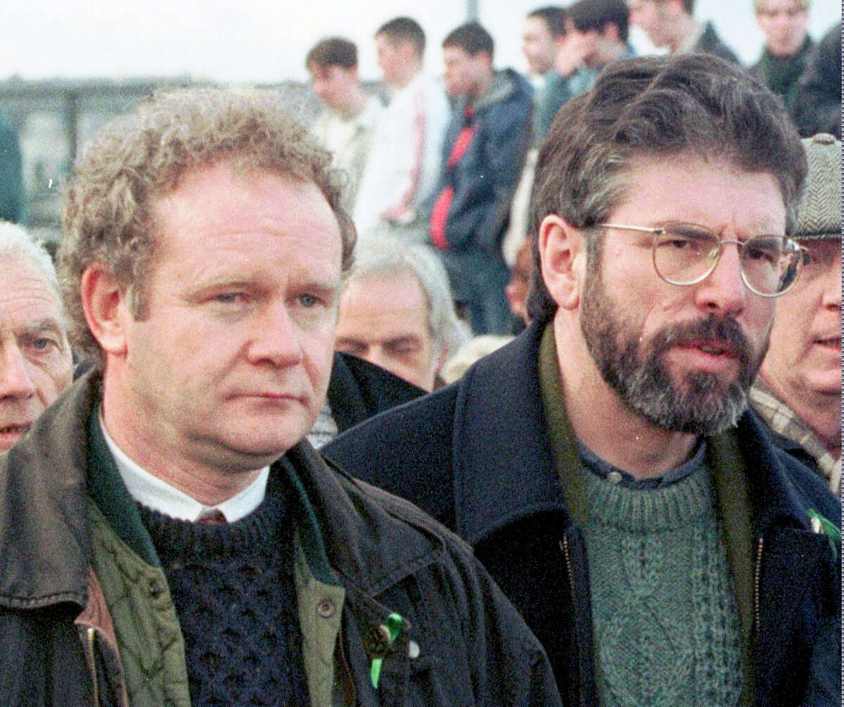FILE - This is a Sunday, Feb. 1, 1998 file photo of Martin McGuinness, the Sinn Fein Chief Negotiator, left, and Sinn Fein's president Gerry Adams as they participate in the Bloody Sunday anniversary march in Londonderry, Northern Ireland. McGuinness, an IRA and Sinn Fein leader who became a minister of peacetime Northern Ireland, has died, according to UK media Tuesday, March 21, 2017 .