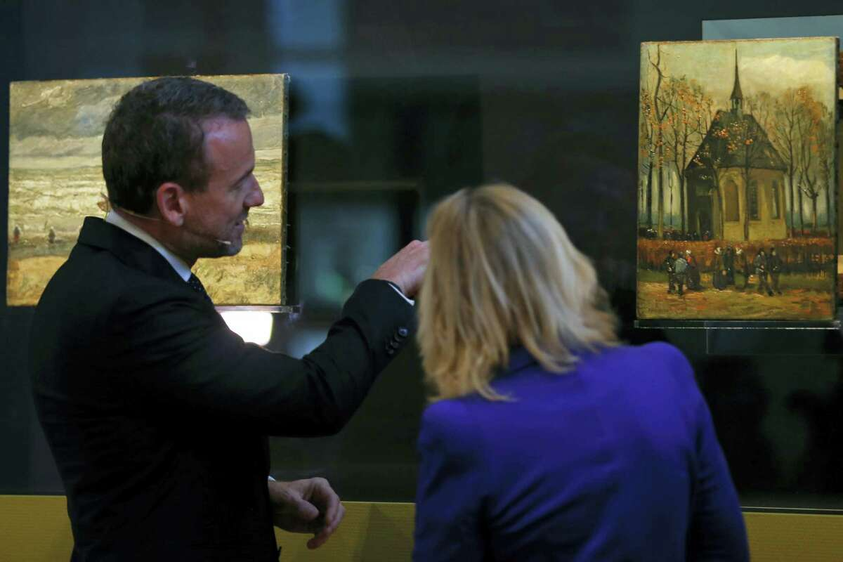 """Van Gogh Museum director Axel Rueger, left, and Jet Bussemaker, Minister for Education, Culture and Science, look at two stolen and recovered paintings by Dutch master Vincent van Gogh during a press conference in Amsterdam, Netherlands, Tuesday, March 21, 2017. The two paintings titled """"Seascape at Scheveningen"""", left, (1882) and """"Congregation leaving the Reformed Church in Nuenen,"""" (1884-1885) returned to the Amsterdam museum after they were stolen from in a nighttime heist 15 years ago and recovered by Naples police in Italy."""