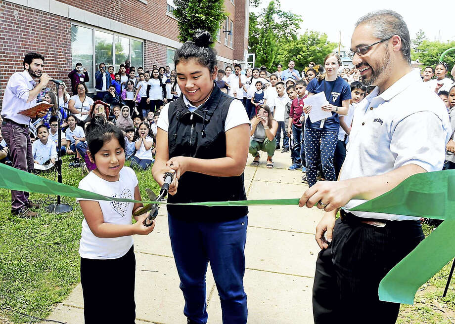 Kindergartner Itzel Rodriguez, 6, left, and seventh grader Erika Velasquez, 13, with the help of their school principal Heriberto Cordero, cut the ribbon during a ceremony celebrating a new schoolyard habitat at the Fair Haven School. Photo: Peter Hvizdak/hearst Connecticut Media   / Peter Hvizdak
