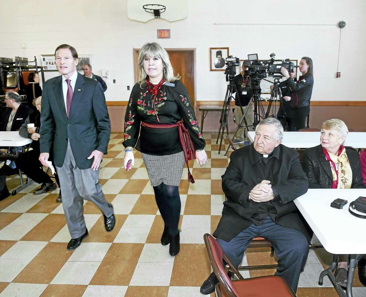 U.S. Sen. Richard Blumenthal, at left, is escorted into St. Michael's Church hall in New Haven by Halia Lodynsky of the Ukrainian Congress Committee of America on Sunday.