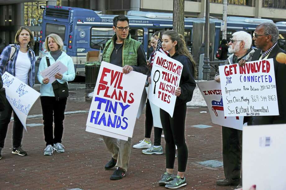 Kate Ramunni -- New Haven Register  Protesters make their points with signs on the Green Sunday afternoon. Photo: Digital First Media