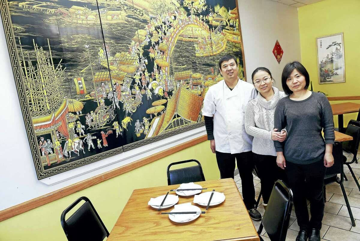 """Left to right, Guangmin Yao, chef and co-owner, his daughter, Jenny Yao, and wife, Xuan Chen, at the newly opened Yao's Diner in Orange last week. They are photographed next to a reproduction of the famous 11th century painting, """"Along the River During the Qingming Festival,"""" by Song dynasty artist Zhang Zeduan."""