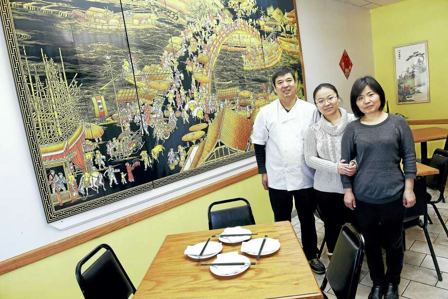 """Left to right, Guangmin Yao, chef and co-owner, his daughter, Jenny Yao, and wife, Xuan Chen, at the newly opened Yao's Diner in Orange last week.  They are photographed next to a reproduction of the famous 11th century painting, """"Along the River During the Qingming Festival,"""" by Song dynasty artist Zhang Zeduan. Photo: Arnold Gold-New Haven Register"""