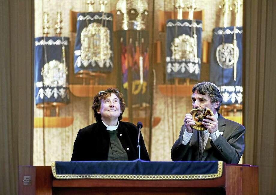 Rev. Daphne Burt, left, recites the Jericho Prayer while Rabbi Herbert Brockman blows the shofar at a meeting about sanctuary congregations. Photo: Arnold Gold — New Haven Register