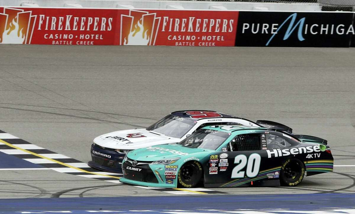 Denny Hamlin (20) edges out William Byron at the checkered line Saturday to win the NASCAR Xfinity series race in Brooklyn, Mich.