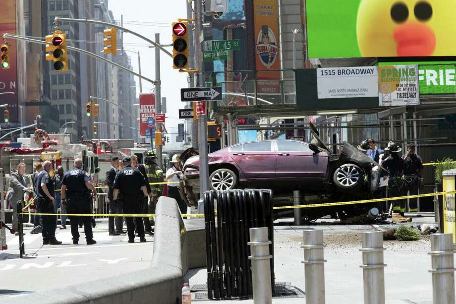 A car rests on a security barrier in New York's Times Square after driving through a crowd of pedestrians, injuring at least a dozen people, Thursday, May 18, 2017. Photo: AP Photo/Mary Altaffer    / Copyright 2017 The Associated Press. All rights reserved.