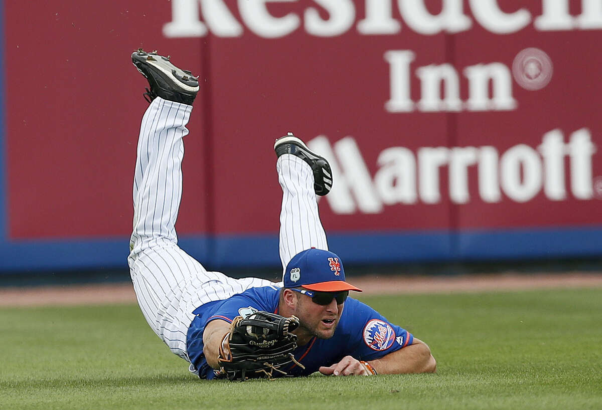 Tim Tebow makes a diving catch during a Mets spring training game.