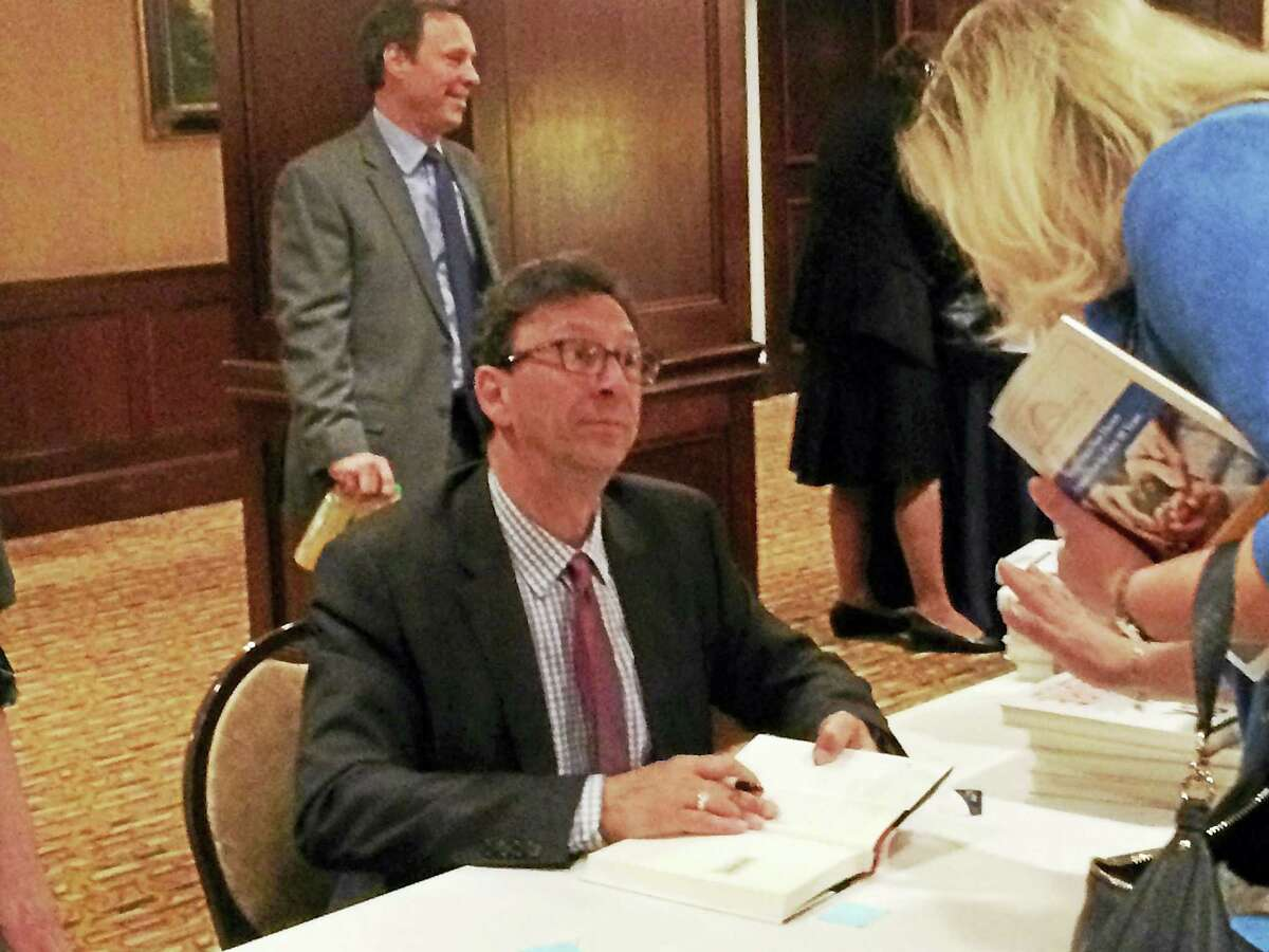 """Former CNN White House Correspondent Frank Sesno signs a copy of his book, """"Ask More: The Power of Questions to Open Doors, Uncover Solutions and Spark Change,"""" after delivering the keynote address at the Greater New Haven Chamber of Commerce Annual Meeting Thursday in New Haven."""