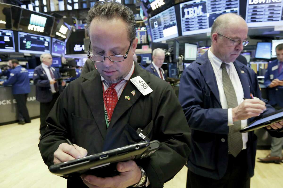 Traders Robert Arciero, left, and Frederick Reimer work on the floor of the New York Stock Exchange Monday.