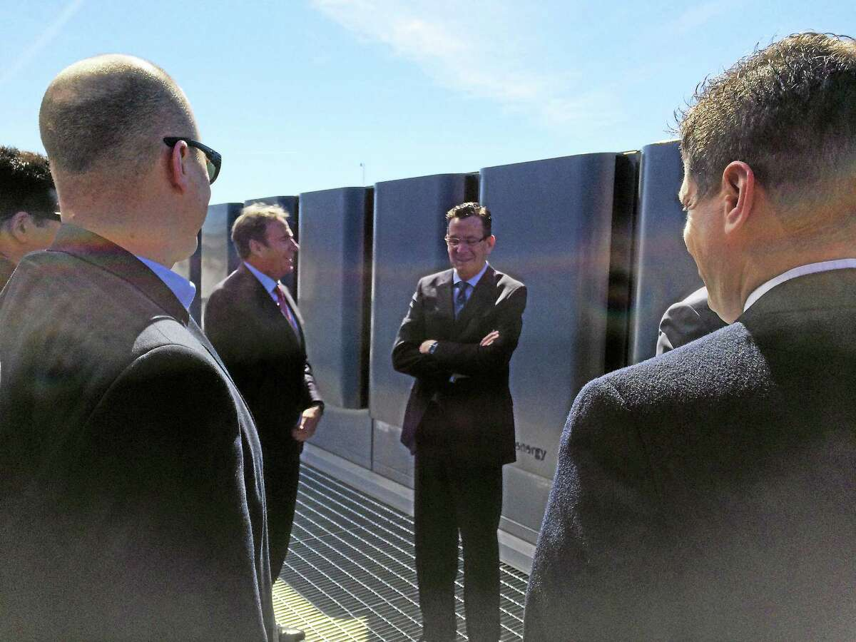 LUTHER TURMELLE — NEW HAVEN REGISTER Connecticut Gov. Dannel P. Malloy, center right, and Bill Kurtz, chief commercial officer for Bloom Energy, center left, chat in front of the company's fuel cell generating equipment Monday at the IKEA store on Sargent Drive in New Haven.