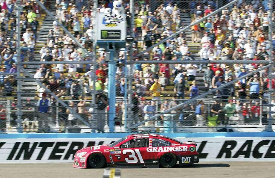 Ryan Newman takes the checkered flag to win Sunday's race at Phoenix International Raceway. Photo: Ralph Freso — The Associated Press   / FR170363 AP