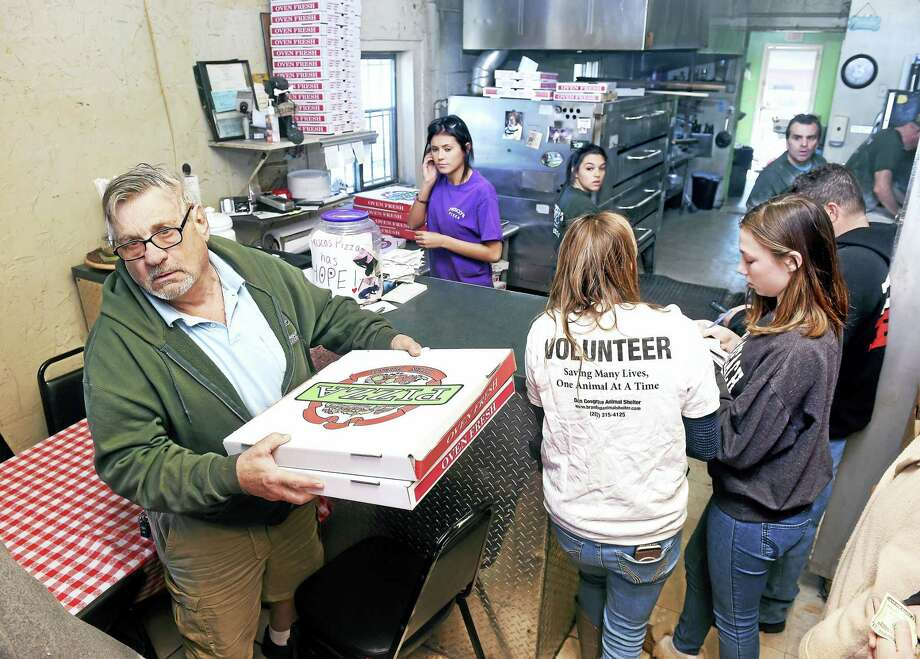 (Arnold Gold-New Haven Register)  George Wolcheski (left) of East Haven leaves Frisco's Pizza in New Haven on 3/19/2017 with some pizza to go during a fundraiser for the dog, Hope, being cared for at the Dan Cosgrove Animal Shelter in Branford. Photo: Digital First Media