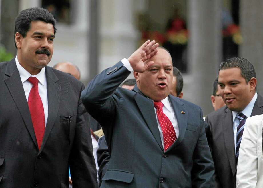 National Assembly President Diosdado Cabello, right, gestures to supporters of President Hugo Chavez as Vice President Nicolas Maduro, left, looks on after a session by lawmakers at the National Assembly in Caracas, Venezuela, Saturday, Jan. 5, 2013. Allies of President Hugo Chavez on Saturday chose to keep Diosdado as National Assembly president who is the next in line to step in as a caretaker leader in some circumstances. Just five days remain until Chavez's scheduled inauguration on Thursday, and government officials are suggesting the swearing-in could be delayed as the president fights a severe respiratory infection after cancer surgery in Cuba. Photo: AP Photo/Fernando Llano    / AP