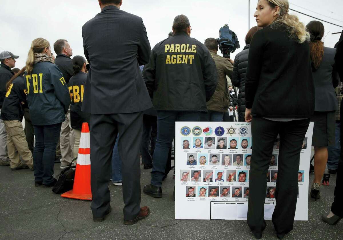 An FBI employee, who declined to give her name, holds a board showing images of MS-13 gang members during a news conference Wednesday, May 17, 2017, in Los Angeles. Nearly two dozen members and associates of MS-13 were arrested Wednesday morning as hundreds of federal and local law enforcement fanned out across Los Angeles, serving arrest and search warrants.