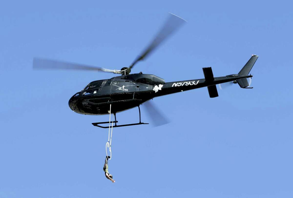 In this Oct. 11, 2015, file photo, Erendira Vasquez Wallenda hangs from a helicopter as she performs before the start of the NASCAR Sprint Cup series auto race at Charlotte Motor Speedway in Concord, N.C. Five years after Nik Wallenda walked over Niagara Falls on a high wire, his trapeze-artist wife is planning to dangle by her teeth from a helicopter as it flies over the falls.