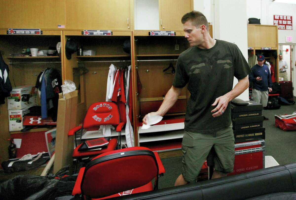 In this Sept. 29, 2011 photo, Boston Red Sox closer Jonathan Papelbon cleans out his locker in the clubhouse at Fenway Park in Boston. The Red Sox have fumigated and disinfected their clubhouse at Fenway Park to help fight the flu. Boston manager John Farrell says it has been done a few times while the team has been on the road. The Red Sox have been hit hard by the bug.