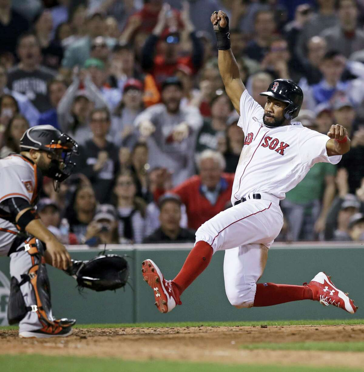 Boston's Chris Young, right, beats the throw home to Baltimore Orioles catcher Welington Castillo, left, while scoring on a single by Dustin Pedroia during the seventh inning at Fenway Park in Boston.
