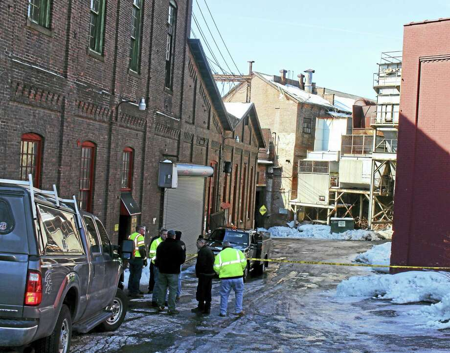 Officials stand near 35 N. Main St. Friday, where a portion of a building came crashing down Thursday afternoon in Ansonia. Photo: Jean Falbo — New Haven Register