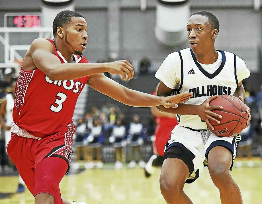Hillhouse's Tyler Douglas looks to make a pass around Wilbur Cross' Marquay McDuffie during Thursday's game in New Haven. Photo: Catherine Avalone — Register   / Catherine Avalone/New Haven Register