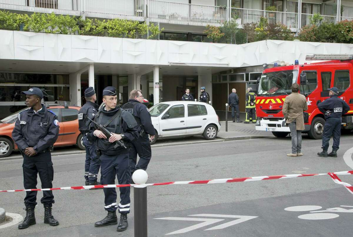 French police secure the entrance of a building in Paris, France, Friday, March 17, 2017. French police officials say a man has been arrested in Paris after fatally slitting the throats of his father and brother. Johanna Primevert, chief spokeswoman for the Paris police department, said she believed the Friday morning killings were part of a family dispute.