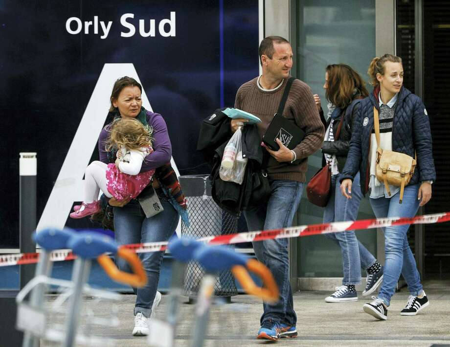 Travelers evacuate Orly airport, south of Paris, Saturday, March, 18, 2017. Soldiers at Paris' busy Orly Aiport shot and killed a man who wrestled one of their colleagues to the ground and tried to steal her rifle Saturday, officials said. Photo: AP Photo/Kamil Zihnioglu    / Copyright 2017 The Associated Press. All rights reserved.