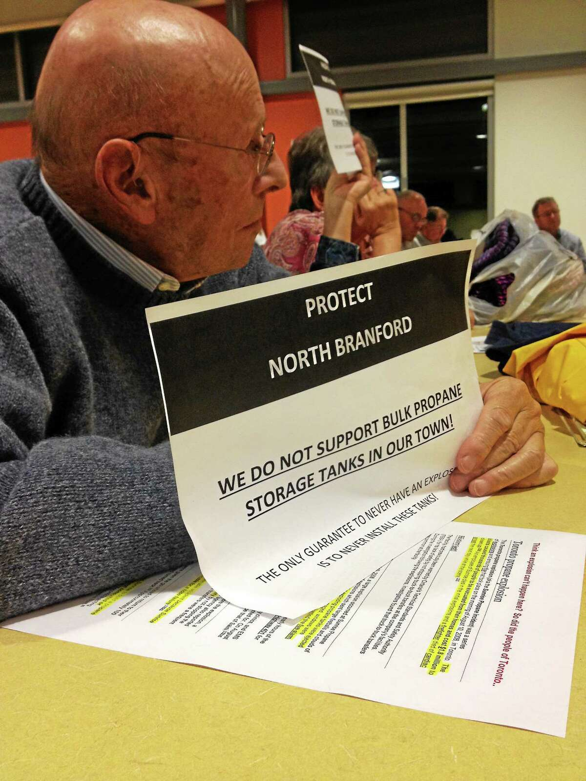 North Branford resident Bob van Marx holds a sign in silent protest at the Planning and Zoning meeting to discuss the J.J. Sullivan's proposed propane facility.