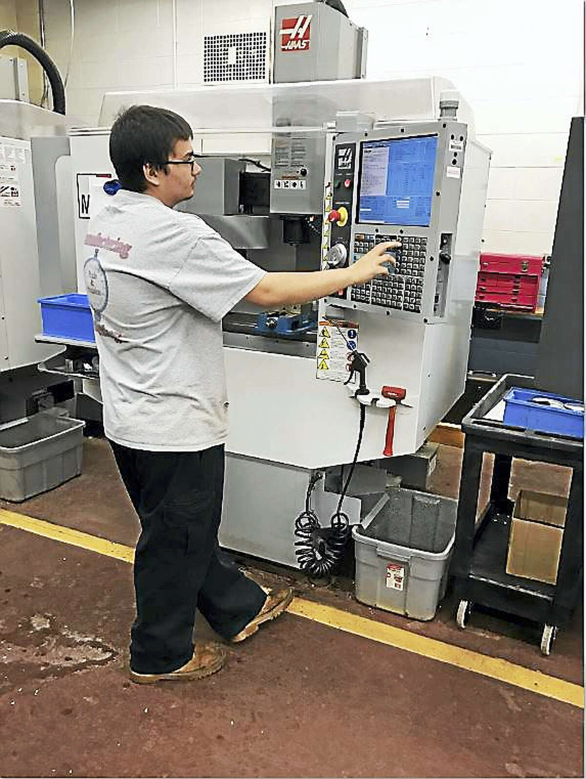 Platt Technical High School student Brian McManus, one of those headed for a national competition, programs a CNC machine.