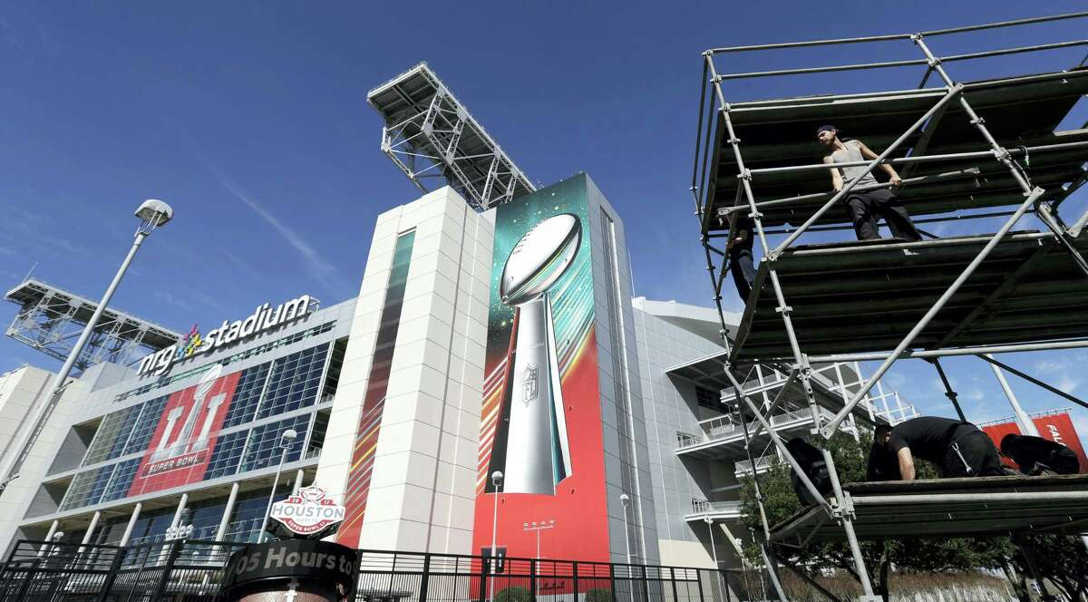 Workers prepare a lighting tower outside NRG Stadium, Tuesday in Houston.