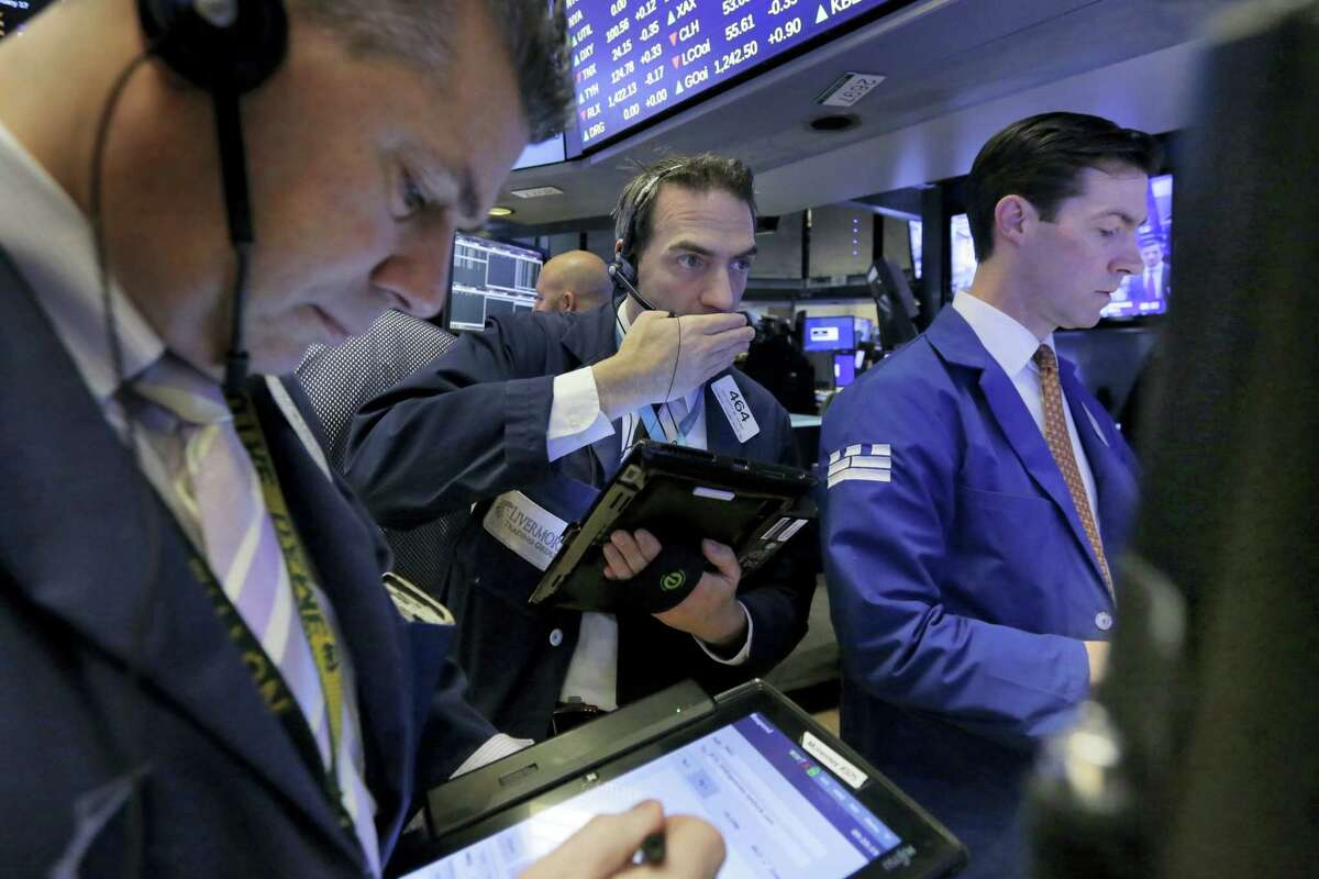 Trader Gregory Rowe, center, works on the floor of the New York Stock Exchange Friday.